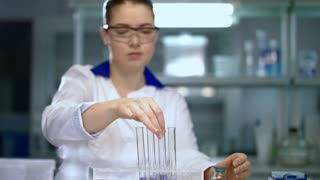 Woman scientist conducting research in chemical lab. Chemist mixing chemical liquid in test tube. Female scientist doing chemical research in research laboratory. Young scientist shaking test tube
