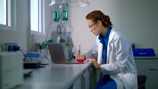 Woman scientist studying chemical liquid in lab flask. Scientist carrying out experiment in research laboratory. Researcher working. Scientist working in research lab. Chemical engineering