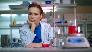 Woman scientist thinking in science laboratory. Woman scientist in lab. Scientist woman looking to laboratory equipment. Young scientist waiting research results