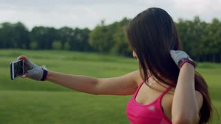 Woman selfie. Asian woman selfi in park. Sport girl taking selfie photo on smart phone outdoors. Closeup of fitness woman posing for selfie portrait. Fit girl using phone for selfie