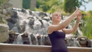 Woman selfie. Young woman taking selfie at park. Selfie woman taking photo outdoor. Blonde girl taking selfie near waterfall. Self portrait. Self photo. Selfie girl posing in sunlight
