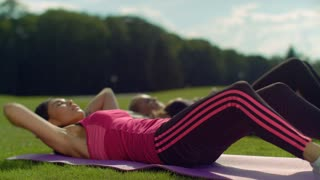 Woman sit ups. Multi ethnic women doing sit up exercise outdoor. Closeup of fitness women workout in park at spring. Outdoor fitness group at sunny day. Chinese woman doing crunch exercise