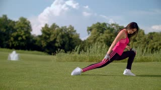 Woman stretching exercise outdoors. Asian woman stretching legs before workout on green grass. Female runner stretching legs. Woman warming up. Fitness woman doing stretching exercise for legs