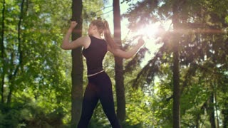 Woman stretching in park at evening. Young female runner warm up outdoor at sunset. Fitness girl doing stretching exercise. Wellness concept. Slim woman in sport clothes workout outdoor at spring