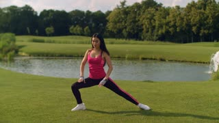 Woman stretching legs before workout on green meadow near pond. Asian girl stretching body on grass near lake. Woman fitness training. Woman warming up legs. Fit girl doing legs stretching exercise