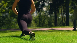 Woman stretching outdoor. Fitness girl doing lunges in park. Workout and fitness. Female runner warm up on green grass. Athletic woman doing squats. Sporty woman doing lunge exercises at sunny day
