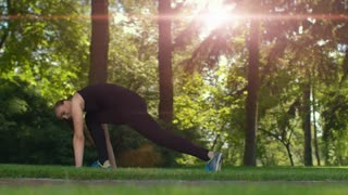Woman training in good mood. Fitness woman doing tilts forward. Sun flare in morning park. Fit girl doing exercises outdoor. Sunlight through trees. Woman dancing. Workout and fitness at sunrise