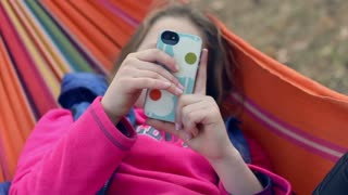 Woman using smartphone lying in hammock. Сloseup. Girl in hammock using smart phone. Young woman with mobile phone in hands. Outdoors recreation. Close up of girl reading message on phone in hammock