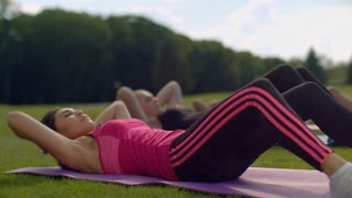 Women group doing sit up exercise outdoor. Close up of asian woman doing sit ups in park. Fitness women training at sunny day. Outdoor fitness training. Chinese girl doing crunch exercise