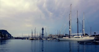 Yacht marina in Barcelona, Spain. Timelapse of yacht port in evening. Time lapse of Barcelona marina. Numerous sail boats in yacht marina under clouds sky. Stormy clouds sky over sea port
