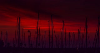 Yacht port at sunrise. Timelapse of yacht marina. Red sky over yacht harbour at morning. Clouds sky. Row of sail masts. Yachts in port at sun rise. Masts silhouettes at red sky in morning sunrise