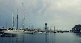 Yachts port, Barcelona, Spain. Timelapse of yacht club at evening. Time lapse of Barcelona marina, Port Vell. Stormy clouds sky in Spain. Numerous sailboats in yacht marina under clouds sky.