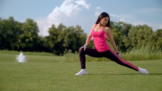 Yoga stretch outdoors. Woman doing stretching exercise in park. Girl stretching legs. Slim woman doing leg stretching exercise on green grass. Healthy lifestyle concept