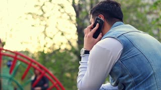 Young guy using phone on playground with children playing in outdoor. Man using smartphone in urban outdoor. Person communicate on mobile phone. Young man in jeans and watch talking on phone