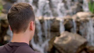 Young man looking at mountain waterfall. Hiker resting near mountain waterfall. Back view of man looking at water falling over rocks. Adventure concept. Close up of young man thinking at nature