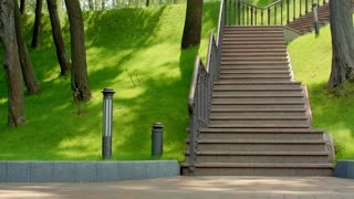 Young man running down stairs in slow motion. Healthy lifestyle concept. Man jogging downstairs. Caucasian man fitness workout. Man running down stairs at park in summer. Fitness training outdoor