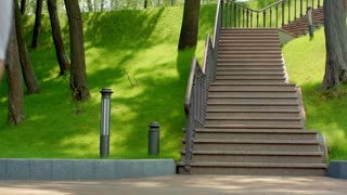 Young man running upstairs in slow motion. Young man running up stairs at park. Man in sport clothes running on staircase. Fitness man workout. Handsome runner climbing stairs
