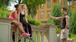Young man taking photo of cheerful girls on phone. Group of friends taking photo on smart phone at summer. Fitness people taking photo after workout. Man taking photo of young women posing on camera