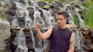 Young man taking selfie. Serious expression on man face. Man selfie. Sef photo of thoughtful man. Handsome man taking photo with phone in park. Man take photo with smartphone camera near waterfall