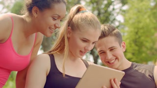 Young people having fun. Friends tablet computer. Closeup of happy friends smiling. Multiracial friends digital tablet. Close up of happy people smiling. Joyful people networking on tablet outdoor