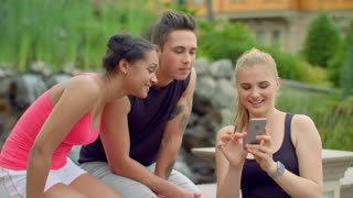Young people watching photos on phone in park. Friends smiling. Happy friends looking photos on smartphone. Multiracial friends having fun together. People phone. Friends using phone