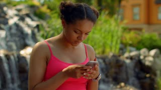 Young woman checking her messages on phone at park. African woman using smart phone outdoor. Closeup of woman texting phone. Woman phone. Mulatto woman networking on iphone. Digital life concept