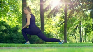 Young woman doing fitness exercises outdoors. Fit girl doing lunges in park. Sun flare in summer park at morning. Workout and fitness in green forest. Attractive woman doing stretching exercises