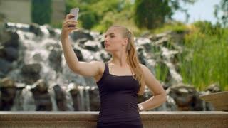 Young woman taking selfie in park. Selfie woman. Woman selfie. Girl taking selfie photo near waterfall. Blonde girl taking selfie on phone. Selfie girl taking photo outdoor. Sporty girl making selfie