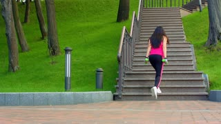 Young woman walking up stairs. Sporty girl climbing stairs. Athletic woman fast walking on staircase. Woman fitness workout with dumbbells. Fit girl go up stairs. Cardio workout. Fitness workout