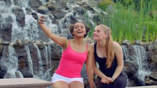 Young women taking selfie near waterfall. Multiracial women taking seflie with phone in park. Joyful women in sport clothes taking self photo. Cheerful girls grimacing and taking self photo with phone