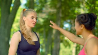 Young women talking in park. Two beautiful girls talking outdoor. Fitness woman talking outdoor. Two girlfriends having fun talking. Multiracial friends resting after fitness workout