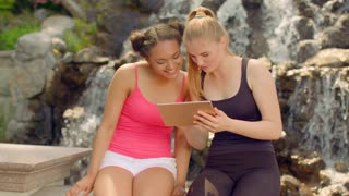 Young women watching photo on tablet outdoor. Friends using tablet computer. Positive girls using ipad in park. Happy women friends laughing. Happy people in nature. Positive girls having fun
