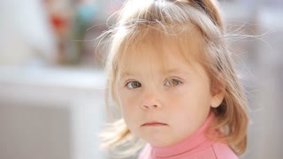 Blue-eyed blonde little girl looking bored and serious