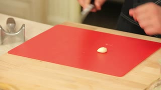Chef Chopping Garlic on the Cutting Board with a Knife