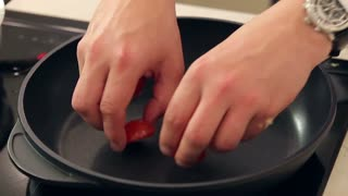 Chef is Putting Half Cut Cherry Tomatoes on a Hot Frying Pan