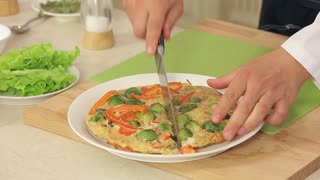 Chef is Serving Omelette with Red Paprika, Brussel Sprouts and Onions with Herbs on a Plate