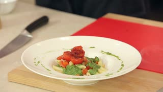 Chef Putting Fresh Basil and Crushed Pepper on Pasta with Green Pesto and Fried Red Cherry Tomatoes in a Plate