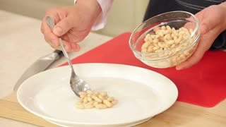 Chef Putting White Beans on a Plate for a Salad
