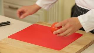 Chef slicing tomato on cutting board