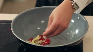 Chef Stewing Garlic, Onion, Ginger and Chili with Soy Sauce in Frying Pan