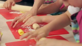 Close up of kids' hands making colorful cookies