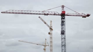 Cranes Working on Construction Site Under Grey Cloudy Sky on a Rainy Day Timelapse