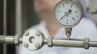 Factory engineer inspecting laboratory pipeline during work