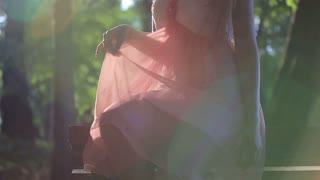 Girl in a Pink Dress Sitting on the Bench on a Sunny Summer Day