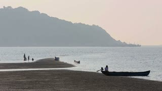Misty tropical seascape with boats and fishermen silhouettes