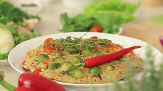Presentation of Omelette with Red Paprika, Brussel Sprouts and Onions with Herbs on a Plate