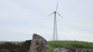 Ruins and wind turbine in the field
