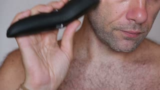 Shirtless man shaving with electric razor