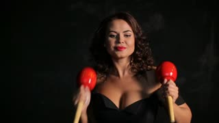 Attractive young brunette musician playing red maracas