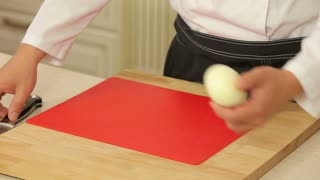Chef cutting up an onion with a knife